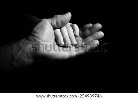 Hand of old and young man in a low key. black and white - stock photo
