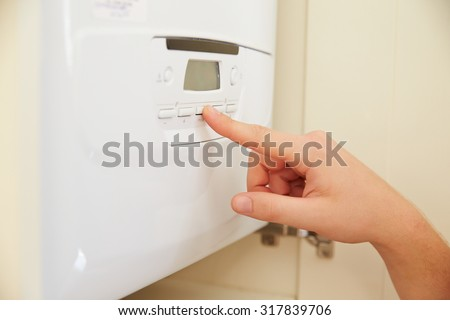 Hand of person using domestic boiler controls, close up