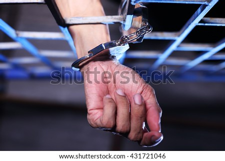 Hand of prisoner in jail - stock photo