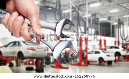 Hand of professional Auto mechanic with wrench. - stock photo