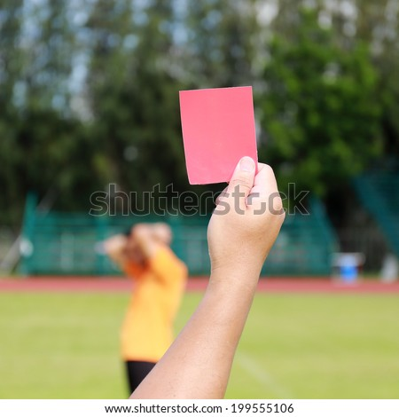 Hand of referee with red card and whistle in the soccer game  - stock photo