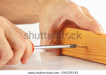 Hand of repairman screws in a wooden block with a screwdriver closeup - stock photo