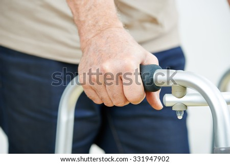 Hand of senior man on a walker in a hospital - stock photo