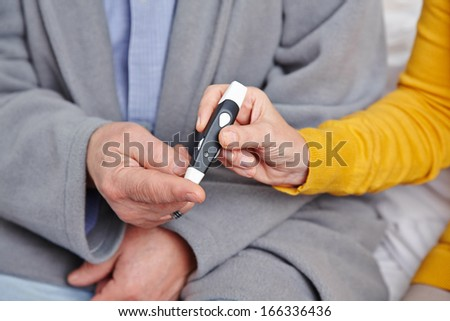 Hand of senior man with diabetes getting blood glucose monitoring - stock photo