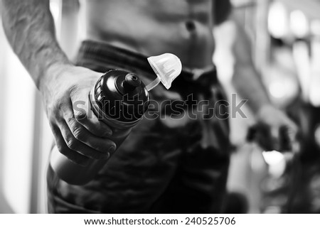 Hand of sportsman holding open plastic bottle with water in gym - stock photo