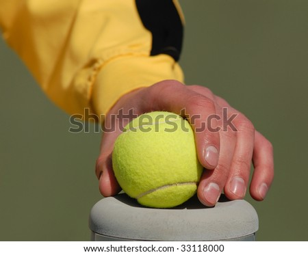 hand of  sportsman holds  tennis ball on  background
