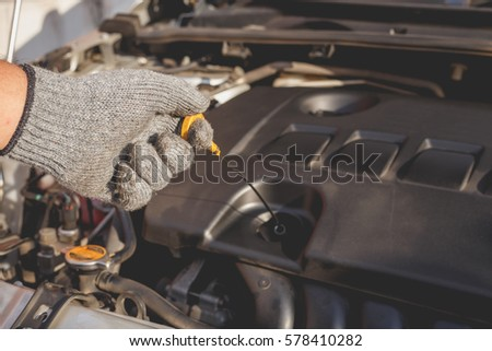 Hand of technician checking or fixing engine of modern car