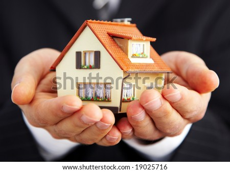 Hand of the businessman with the house... - stock photo