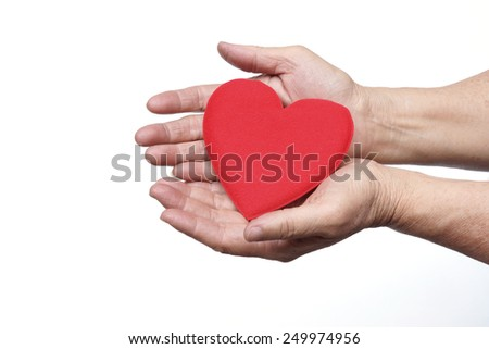 hand of the elderly female holding a red heart