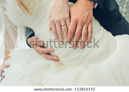 Hand of the groom and the bride with wedding rings - stock photo