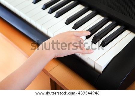 Hand of the Kid on the Piano Keyboard