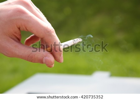 hand of the man with a smoking cigarette