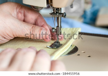 hand of the old woman put to thread a needle sewing machine - stock photo