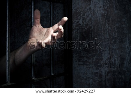 Hand of the prisoner on a steel lattice close up - stock photo