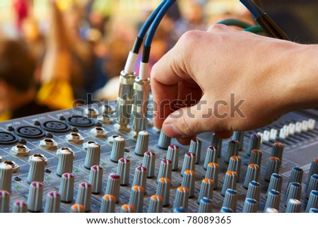Hand of the sound producer and mixer console - stock photo