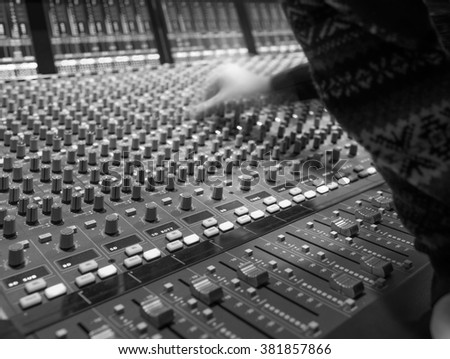 Hand of the sound producer,Professional audio mixing console with faders and adjusting knobs - radio / TV broadcasting, sound mixer with buttons and sliders,Shallow Depth of Field and Selective Focus - stock photo