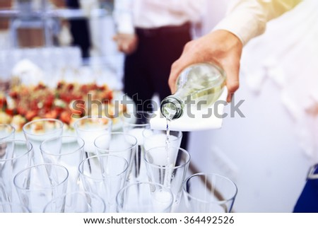 Hand of the waiter pours white wine in wineglass. Bright picture of pouring wine into glasses. - stock photo