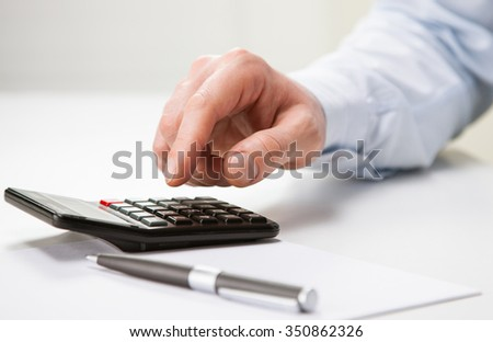Hand of unrecognizable businessman using calculator - closeup shot - stock photo