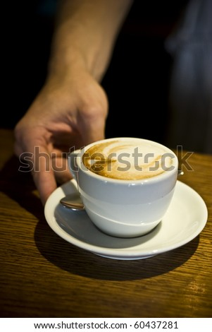 Hand of waiter serving a cup of cappucino - stock photo