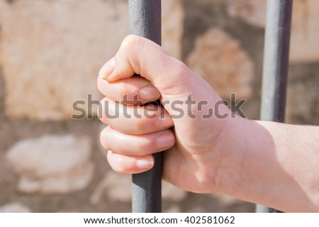 hand of woman holding the iron bar at the prison