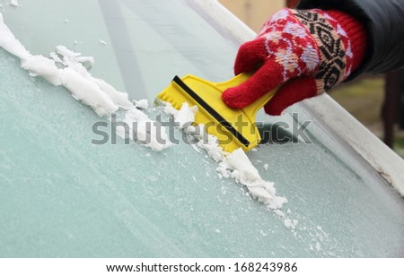 Hand of woman in glove scraping ice and snow from car windscreen - stock photo