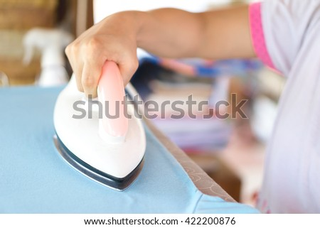 hand of woman ironing clothes on the table