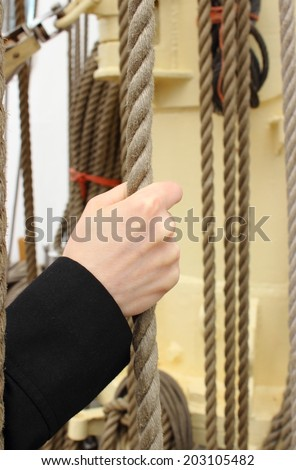 Hand of woman pulling nautical thick rope on the yacht - stock photo