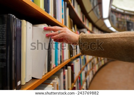 Hand of woman selecting a book from book shelf - stock photo