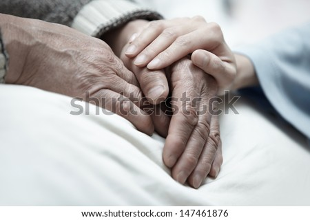 Hand of woman touching senior man in clinic - stock photo