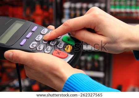 Hand of woman using payment terminal in an electrical shop, enter personal identification number, finance concept