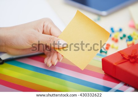Hand of woman with yellow adhesive note