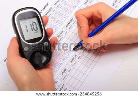 Hand of woman writing data from glucometer to medical form, result of measurement sugar, concept for measuring sugar level - stock photo