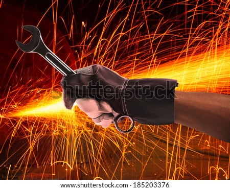 hand of worker man working by leather hand glove protection heat of splashing fire in heavy industry factory use for metal and iron industrial manufacturing theme  - stock photo