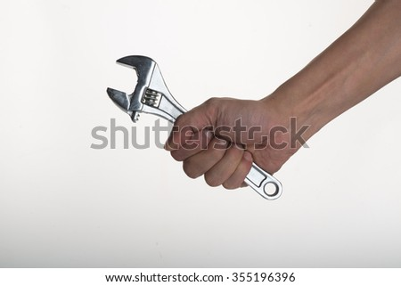 Hand of worker with a wrench closeup - stock photo
