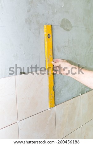 Hand of worker with spirit level. repair, building, technology and home concept - stock photo