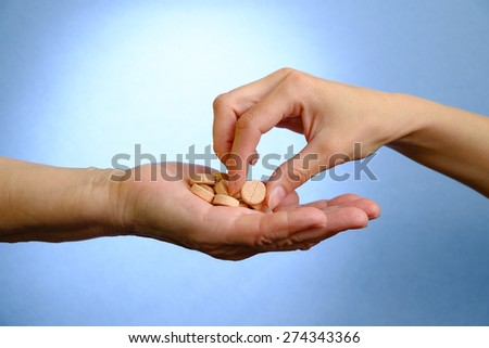 Hand of young woman and elderly woman holding the pills - stock photo