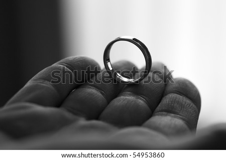 Hand offers wedding band - stock photo