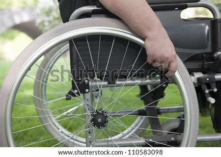 hand on a a wheel of wheelchair