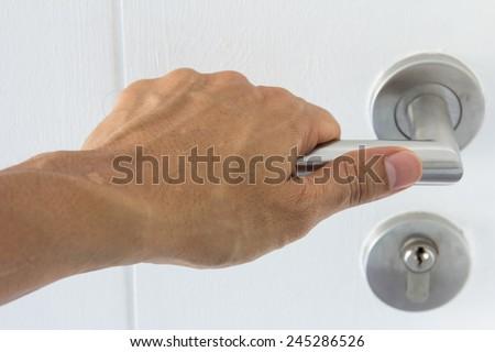 Hand on a handle wooden door to open  - stock photo