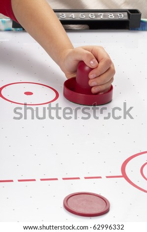 Hand on a mallet over air hockey table - stock photo