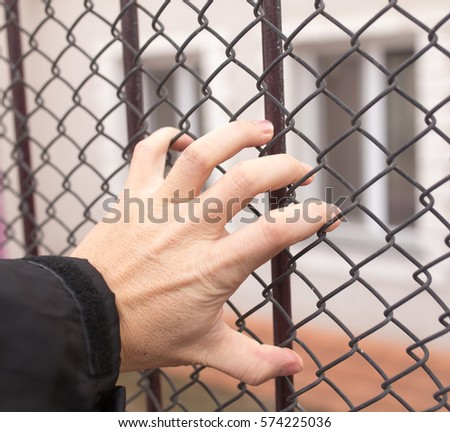 hand on a metal fence