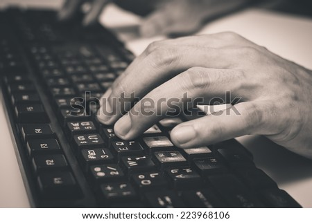 hand on Asian language computer keyboard , old B&W film processed / office syndrome for healthcare and business concept - stock photo
