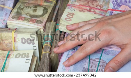 Hand on bundles of banknotes - stock photo