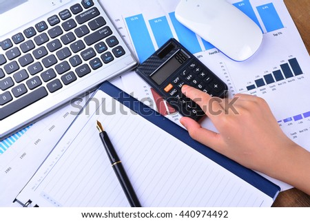 Hand on calculator with graph, chart, keyboard, mouse on wooden table - stock photo