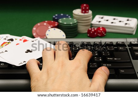 hand on computer keyboard with playing cards chips and dices in background - stock photo