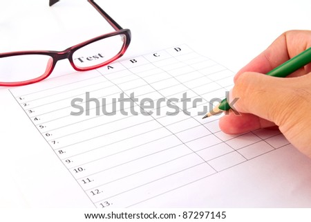 Hand on pencil choosing the test list and glasses on the examination