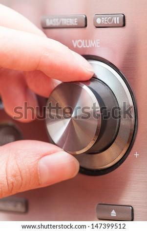 Hand on Sound volume control knob - stock photo