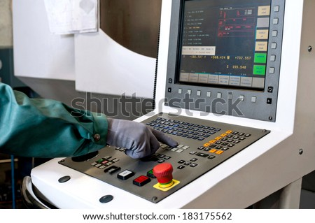 Hand on the control panel of a computer numerical control programmable machine. Milling industry. CNC technology. - stock photo