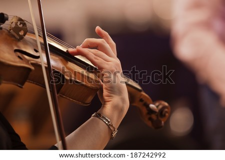 Hand on the strings of a violin - stock photo