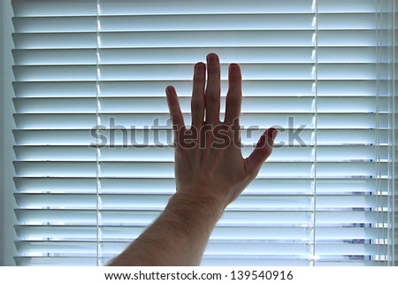 Hand on white blinds background - stock photo